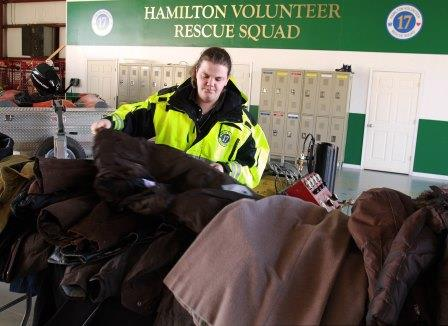 A volunteer with a large pile of donated coats