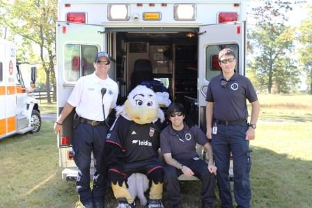Three Company 17 volunteers in front of the ambulance with the FARE mascot