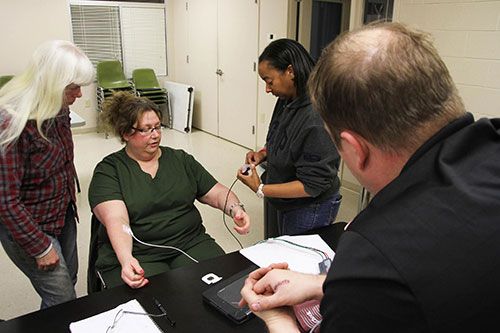 Member applying electrodes to a volunteer mock patient.