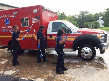 Three volunteers washing an ambulance